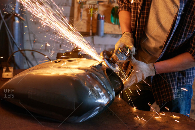 Unrecognizable man using grinder repairing motorcycle fuel tank