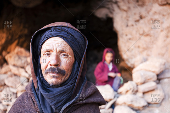 Attribute, Souses-Massa, Morocco - April 9, 2012: A Cave used as a nighttime shelter for goats and sheep in the Anti Atlas mountains of Morocco, North Africa with the Berber shepherd and his son.