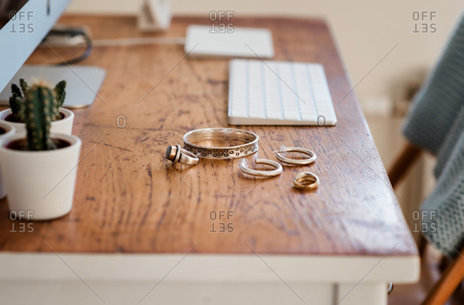 Woman's silver jewelry on a desk next to a computer