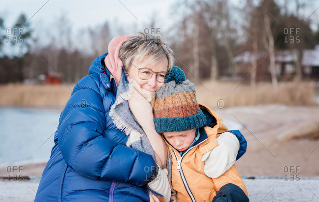 grandmother comforting her grandson whilst playing outside in winter