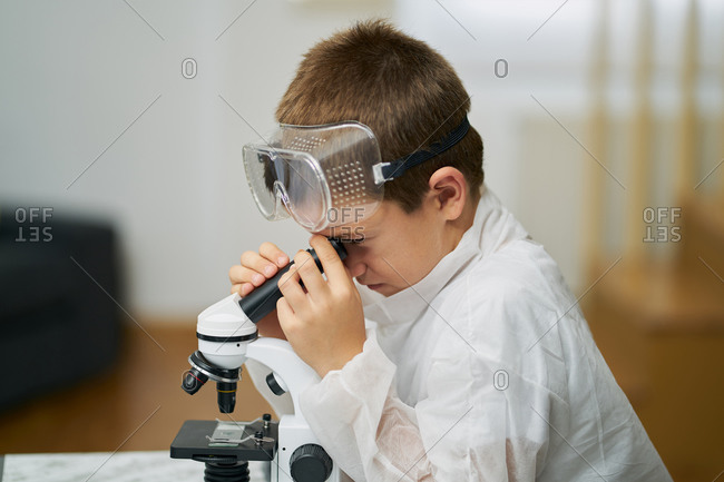 young boy dressed in a white robe and protective goggles observes thro