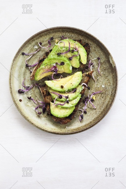 Healthy vegetarian or vegan snack of fresh avocado on toast.