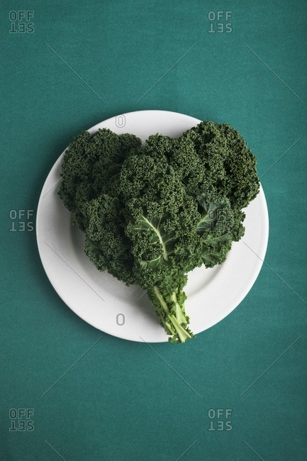 Heart shaped kale leaves on a white plate