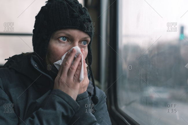 Woman blowing her nose with a tissue on a bus