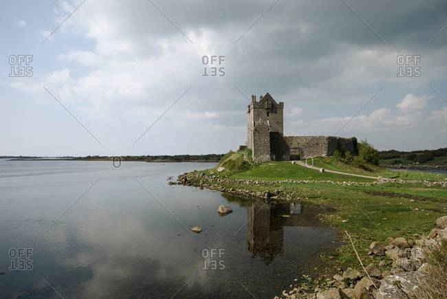 Old grey stone tower on green coast of calm lake with cloudy sky in background