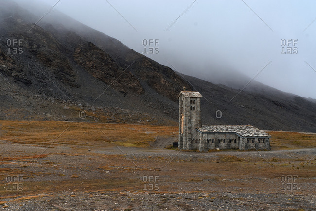 Long old stone building with high tower among deserted terrain with mountain in foggy weather