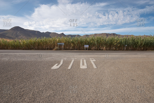 From above of inscription stop on asphalt road with tall grass mountains and blue sky in background