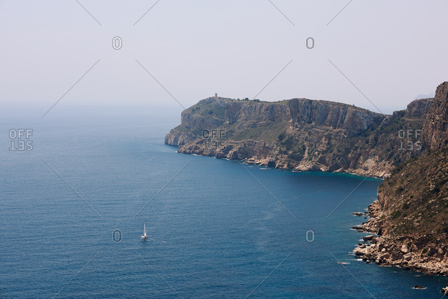 Aerial view of white yacht in blue endless ocean near rocky island under foggy sky