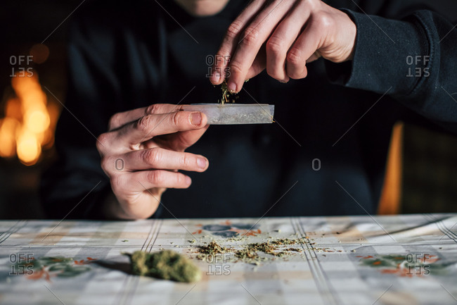 Close-up of a man's hands preparing marihuana joint
