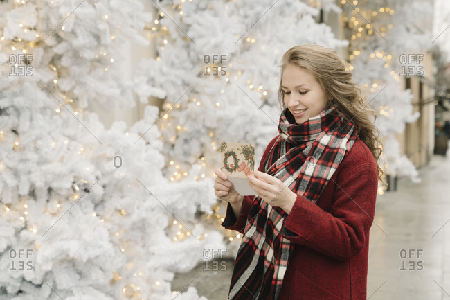 Portrait of smiling young woman standing on the street with Christmas card in front of white Christmas trees