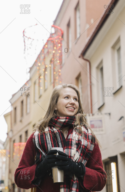 Portrait of smiling young woman with travel mug at Christmas time in the city