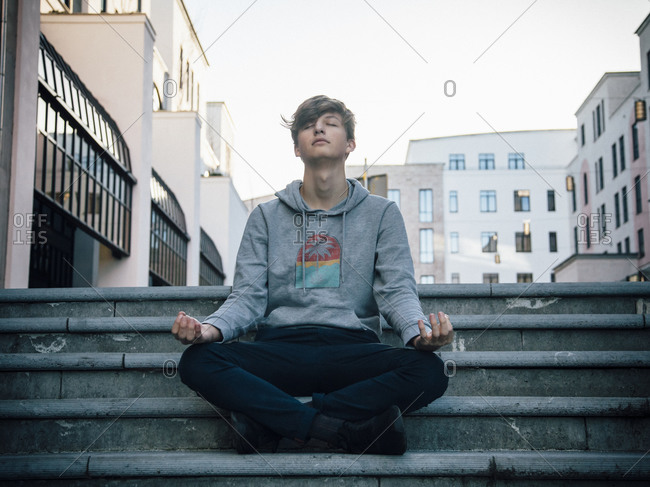 Teenager sitting on steps meditating in the city