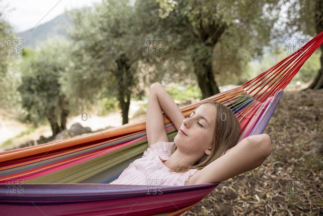 Girl resting in hammock in an olive grove