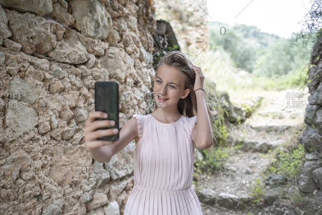 Girl taking selfie next to an old stone wall- France
