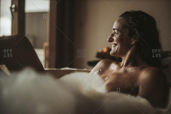 Happy woman relaxing in bathtub