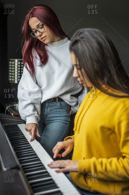 Two teenage girls practicing piano