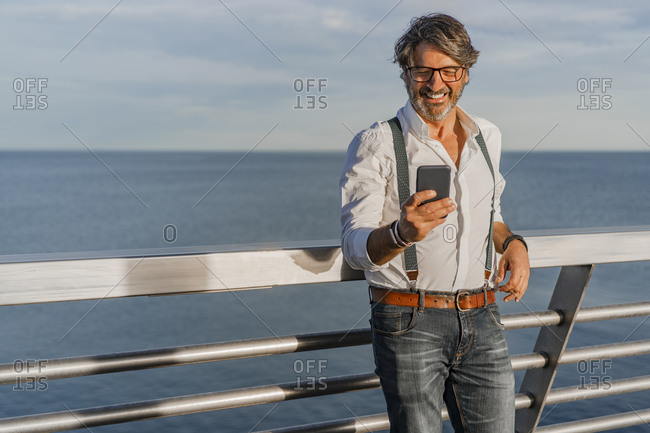 Smiling man using smartphone on a jetty