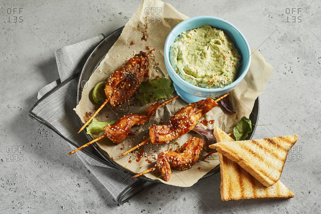Toasts- grilled chicken skewers and bowl of salsa verde sauce