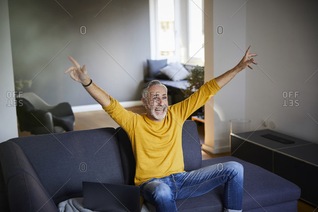 Mature man sitting on couch at home cheering