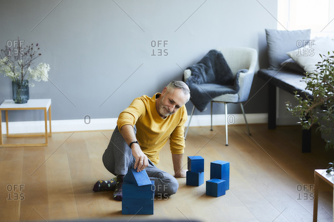 Mature man playing with building blocks on the floor at home