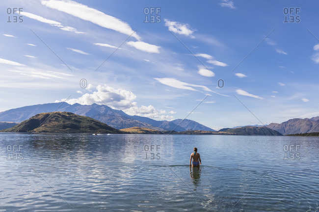New Zealand- Queenstown-Lakes District- Glendhu Bay- Female tourist standing waist deep in Lake Wanaka