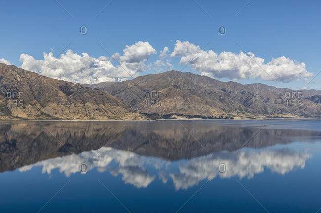 New Zealand- Queenstown-Lakes District- Wanaka- Hills and blue summer sky reflecting in Lake Hawea