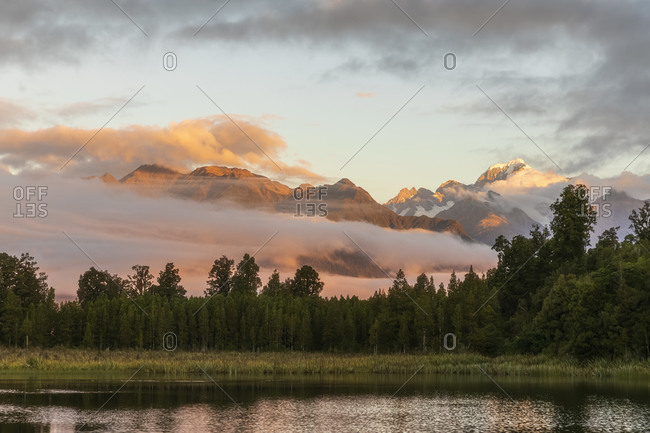 New Zealand- Westland District- Fox Glacier- Lake Matheson at dawn with mountains shrouded in fog in background