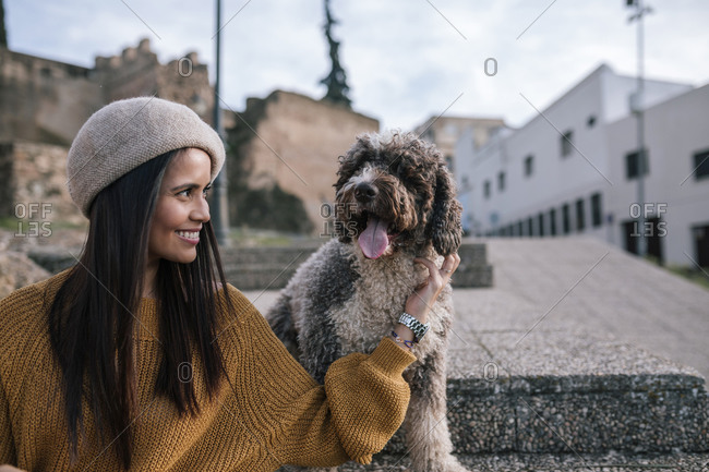 Happy young woman stroking her dog in the city