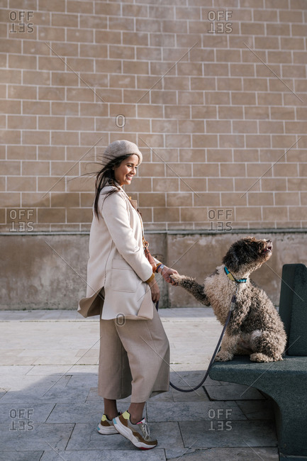 Young woman with her dog in the city giving paw