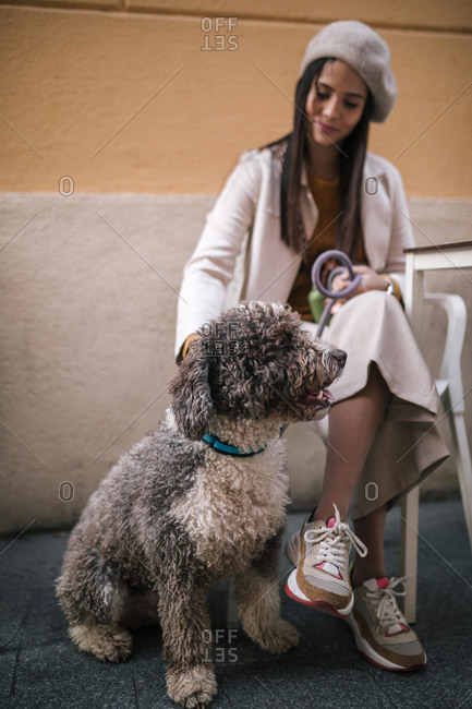 Young woman sitting with her dog in a cafe in the city