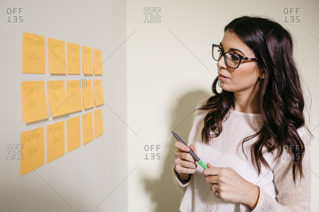Young woman in office looking at a wall with adhesive notes