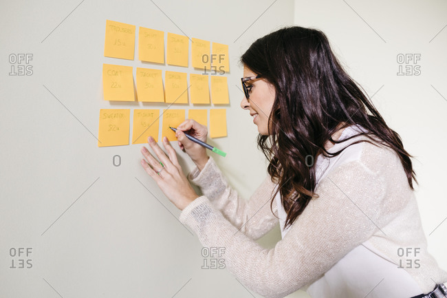 Young woman standing in office at a wall taking notes on adhesive notes