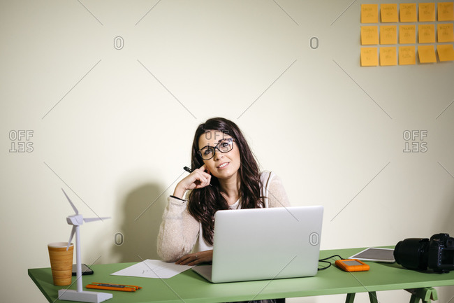 Young woman sitting at desk in office thinking