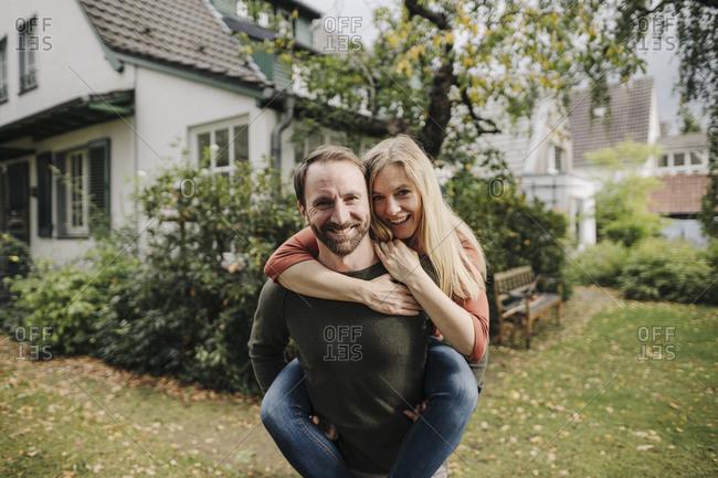 Man carrying happy woman piggyback in garden
