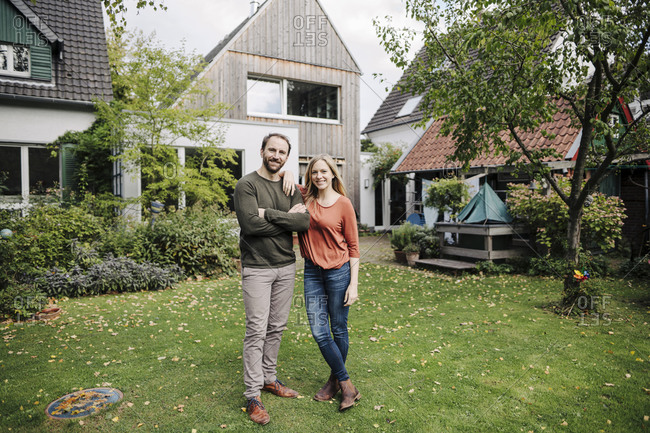 Proud home owners standing in their garden