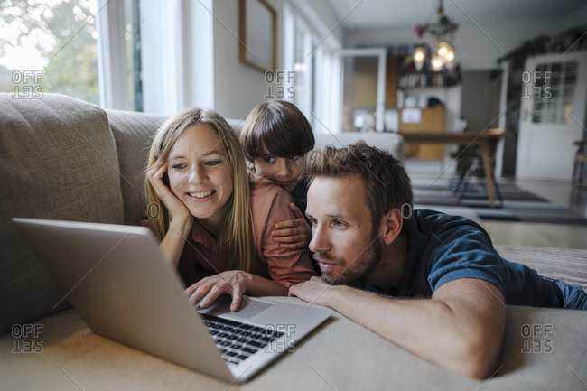 Happy family lying on couch- using laptop