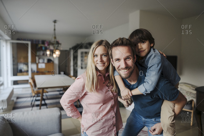 Happy family standing in living room- smiling at camera