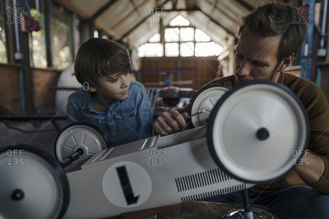 father and son repairing toy car in the barn