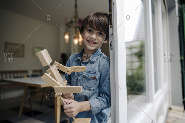 Little boy standing by window- holding self-made toy robot