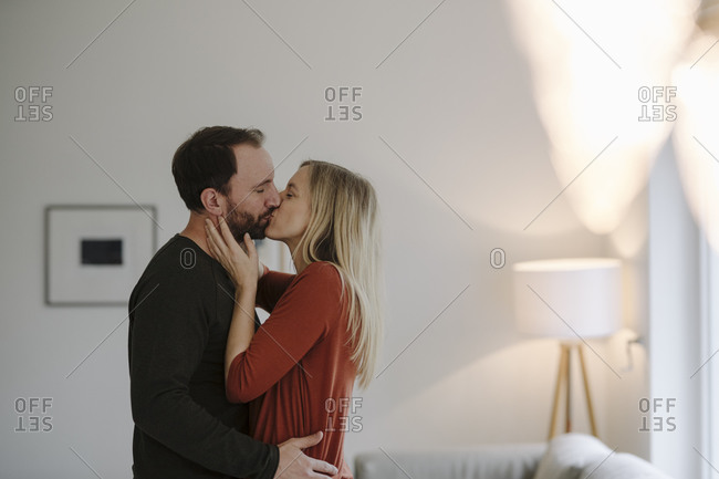 Happy couple embracing and kissing in their comfortable home