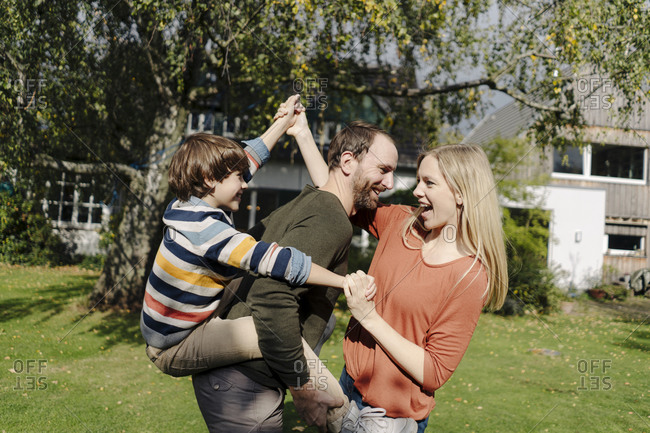 Parents and son having fun- playing in the garden