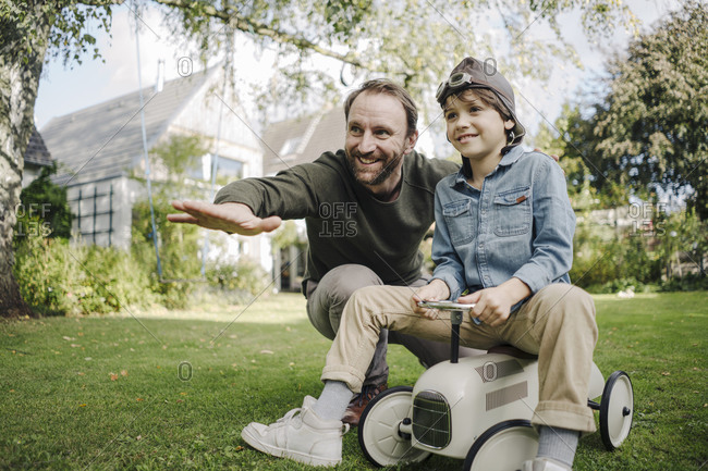 Father and son playing with toy car in the garden