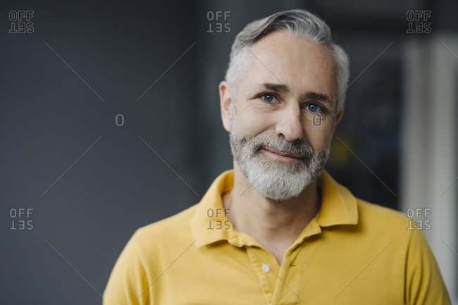 Portrait of smiling mature man with grey beard and blue eyes