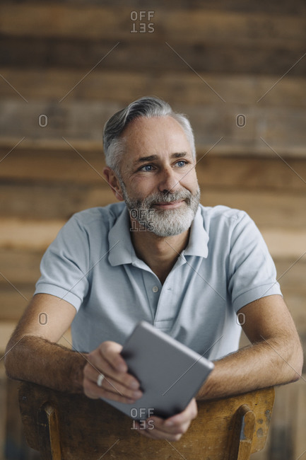 Portrait of smiling mature man with digital tablet leaning on back rest looking at distance