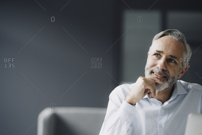 Portrait of pensive mature businessman in his office looking at distance