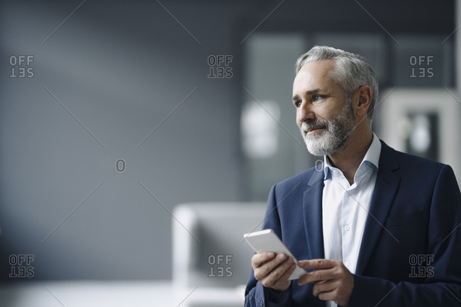 Portrait of smiling mature businessman with smartphone looking at distance