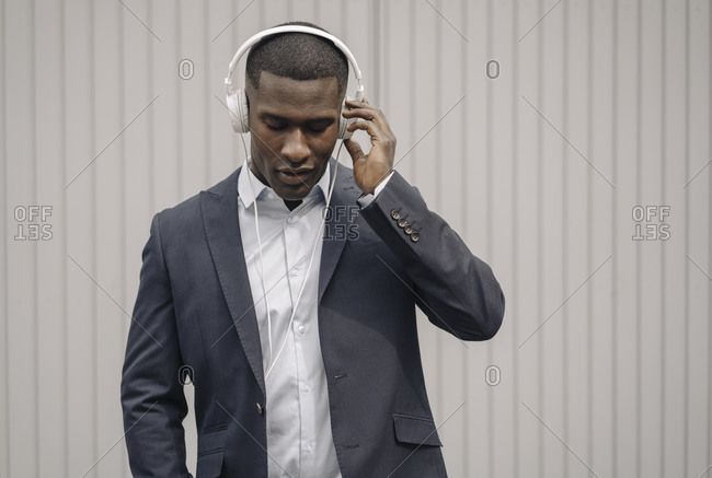 Portrait of young businessman with eyes closed listening music with headphones outdoors