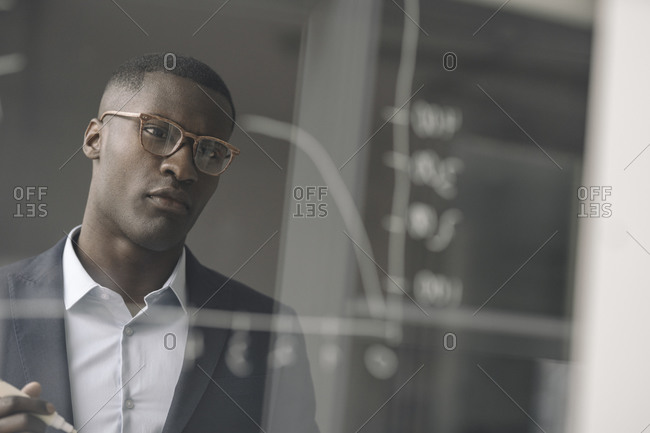 Portrait of young businessman looking at diagram on glass pane in office