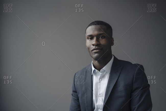 Portrait of young businessman against grey background