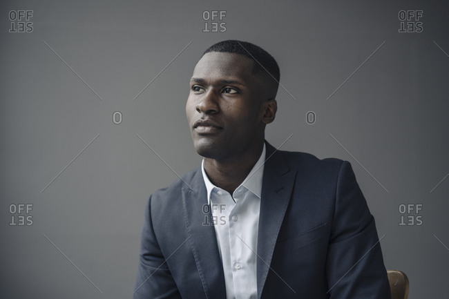 Portrait of young businessman against grey background looking at distance